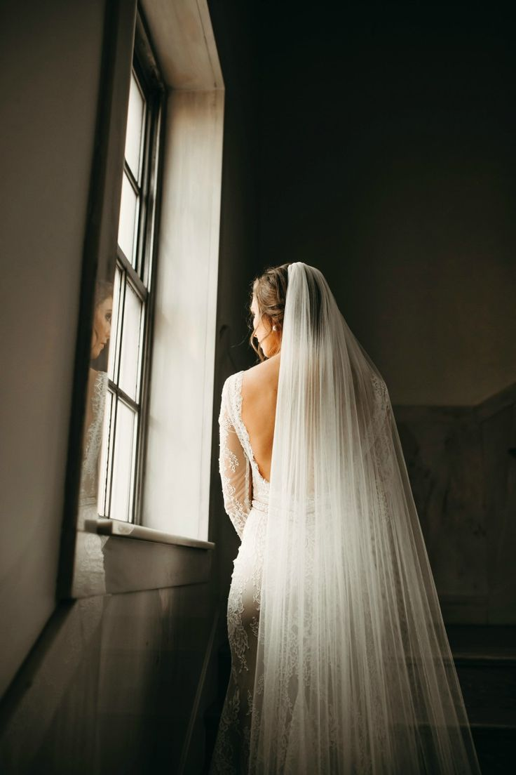 bring natural light inside with a beautiful window || stairs, stairwell, lace, veil, braid, fishtail, bride, bridal portraits, pose, ideas, window sill, reflection