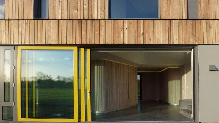 Неоново-желтые автоматические стеклянные двери добавляют нотку энергии экологичному дому, находящемуся на восточном побережье Ирландии.