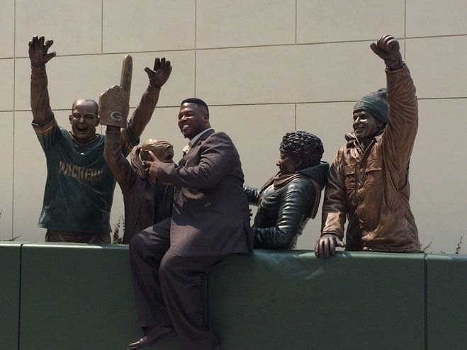 LeRoy Butler poses on a new statue honoring the Lambeau Leap.