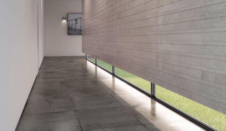 Hal met grote, donkerbruine vloertegels met betonlook.