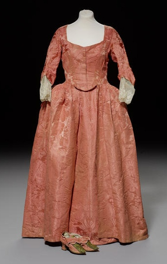 An 18th century two toned salmon pink damask Robe, circa 1775, England. woven with large exotic foliage, centre front fastening, cartridge pleated waistline, three quarter length sleeves, and a matching petticoat front, together with a pair of self covered fabric shoes with Louis heel, pointed toes and central braidwork decoration to vamps. Bonhams