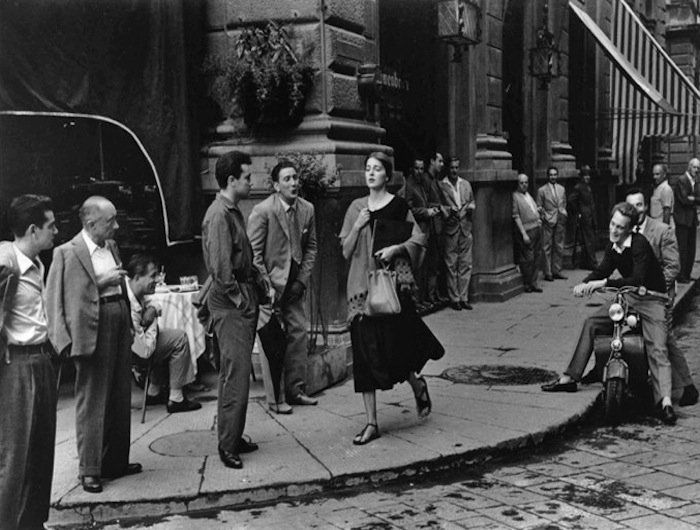 """American in Italy"" — Then This photograph of more than a dozen men ogling a beautiful woman was shot in Florence, Italy in 1951. In the aftermath of WWII, Nanalee Craig, then 23, quit her job to travel alone around Europe. In Florence, she met another female traveler, Ruth Orkin, who was a photographer and would end up snapping the iconic shot."