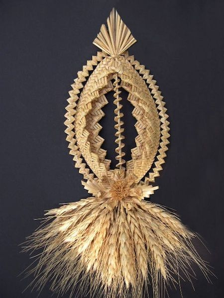 a braided straw artwork with a spheroid shape up town and straw tassels