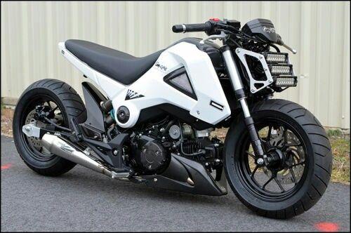 white Honda Grom custom with triple LED head light array and extended swingarm