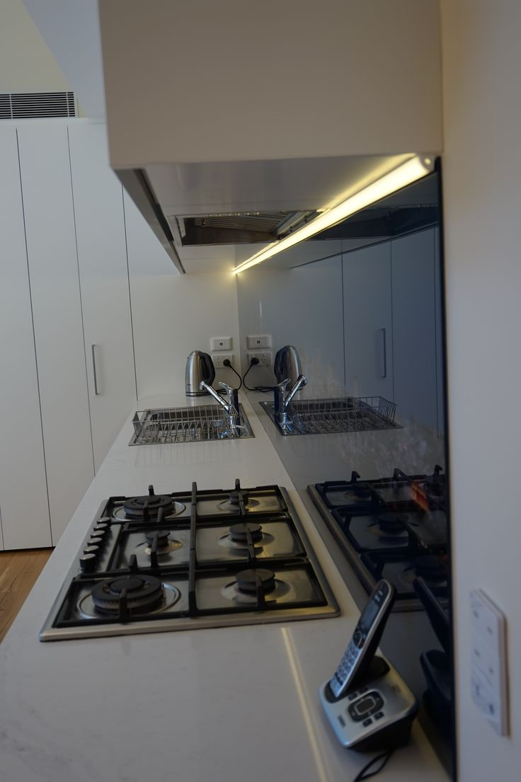 View of cook top and sink plus the concealed range hood