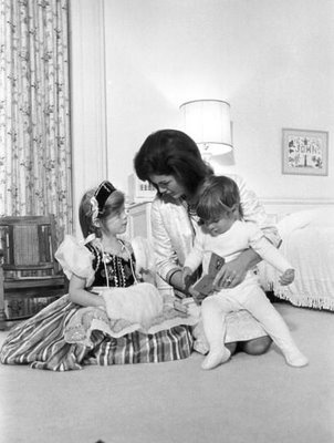 First Lady Jacqueline Bouvier Kennedy reading to her children, John F. Kennedy Jr. and Caroline Kennedy. Caroline wears a medieval costume dress and a headband, 1962. Photo John F. Kennedy Library/Getty Images