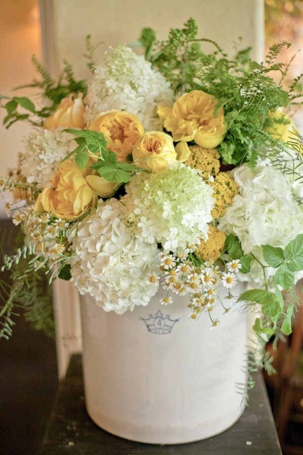 Hydrangea, yarrow, chamomile, and roses in a crock