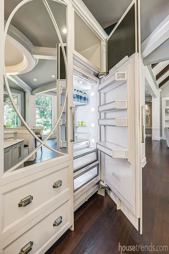 This 60-inch Thermador refrigerator features custom door panels with mirrors that reflect the unique design of the round island and ceiling details in the Chateau Sérendipité by G.A. White Homes, from Dayton Homearama 2016.