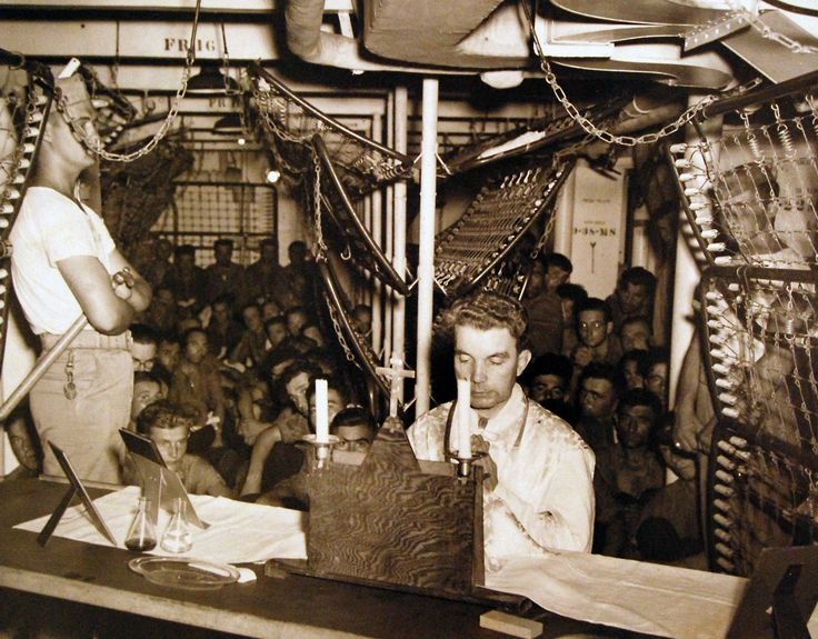 Normandy Invasion, D-Day, June 1944. USS Arkansas (BB 33) – German prisoners of war onboard for transportation from Southern coast of France to a prison camp. Shown: Chaplain T.J. Fallon, holding church services. August 20, 1944. Official U.S. Navy photograph, now in the collections of the National Archives.