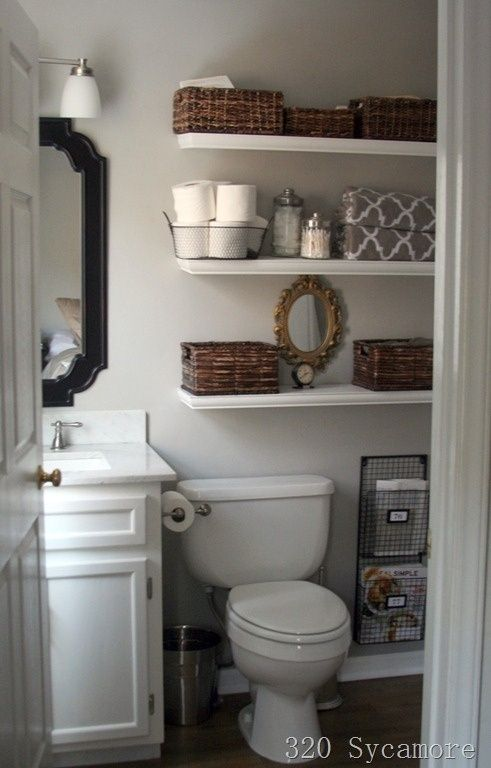 small bathroom- like the shelves and the use of the wood baskets to soften the white. Like the magazine rack too.