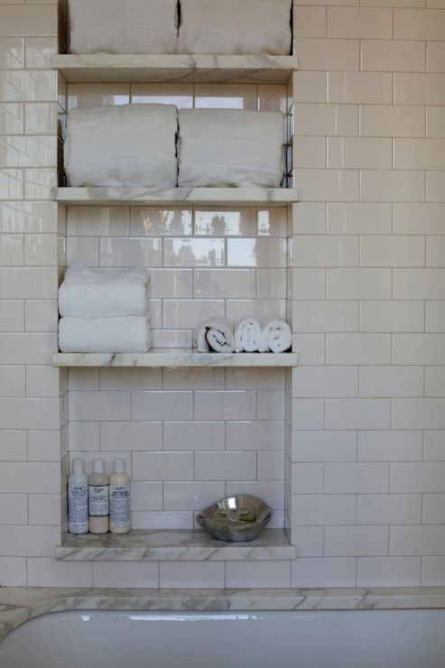 Gorgeous bathroom features drop-in bathtub lined with white marble surround and ivory subway tile shower surround. Shower with niche accented with marble shelves filled with towels and bath accessories.