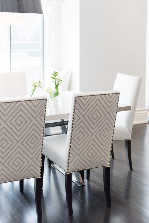 A black drum pendant with crystals illuminate a gray x-based dining table lined with white and gray diamond pattern leather dining chairs.