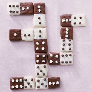 Double-Dipped Dominoes This cookie recipe uses miniature white and dark candies to create domino-looking petit four treats.