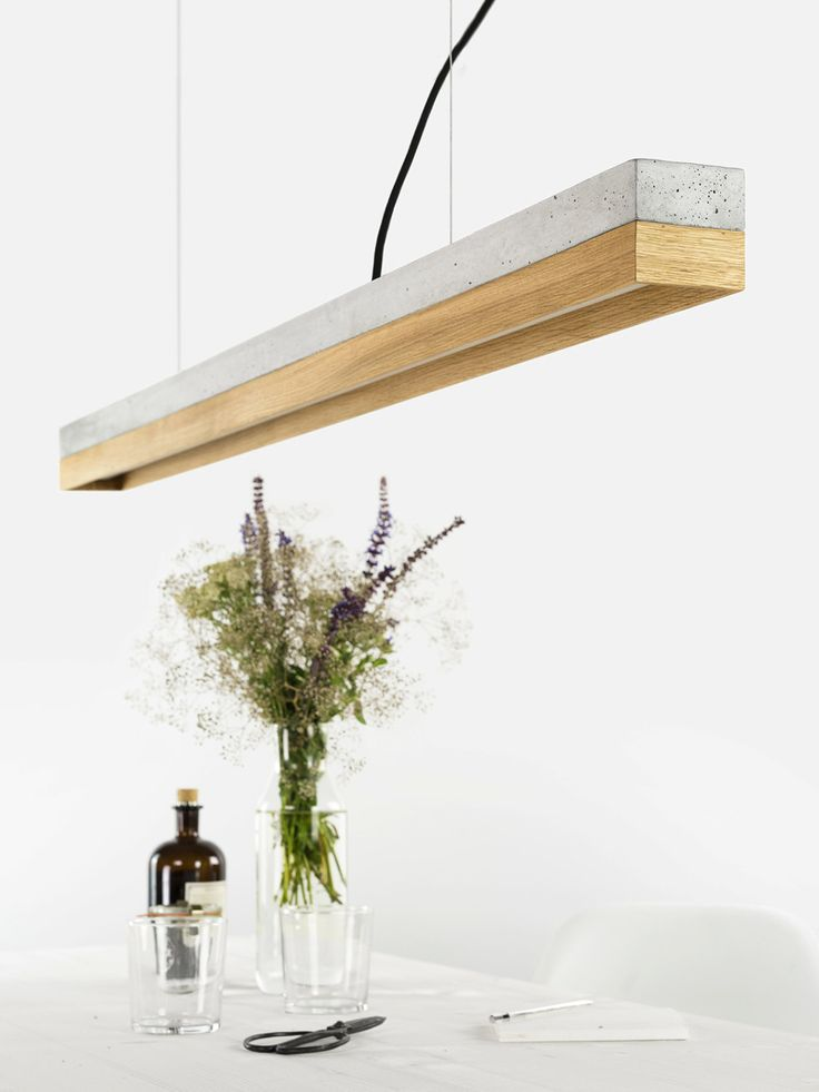 [C1]oak Die rechteckige Hängelampe [C1] wird aus einem hellgrauen Beton gegossen. Sie kombiniert naturbelassenes Eichenholz mit rauem Beton zu einer zeitlosen und eleganten Designerleuchte. Die unterschiedlichen Materialien der Lampenschirme lassen sich individuell kombinieren und können jederzeit getauscht werden. Mit der Kantenlänge von 122 x 8 x 8 cm eignet sich die Lampe besonders gut sie über einen Esstisch oder einer langen Tafel in Szene zu setzen. Auf Grund ihres minimalistischen…