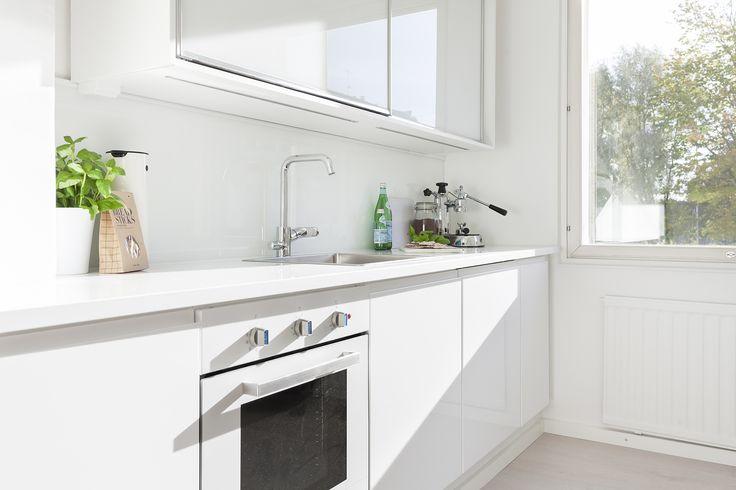 Kaunis valkoinen koti Turussa. Inarian liukuovikaapisto keittiön yläkaappina. #valkoinen #keittiö #liukuovet #keittiökaapit