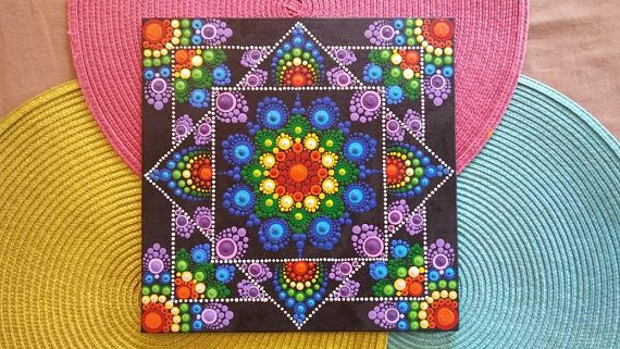 Hand painted 10x10-inch Rainbow inspired dot mandala painting on canvas panel. Painted with black background and dotted using colors found in rainbow. This piece looks as if there is a mandala stacked on another. This would be a beautiful piece hanging in your home/office or propped up