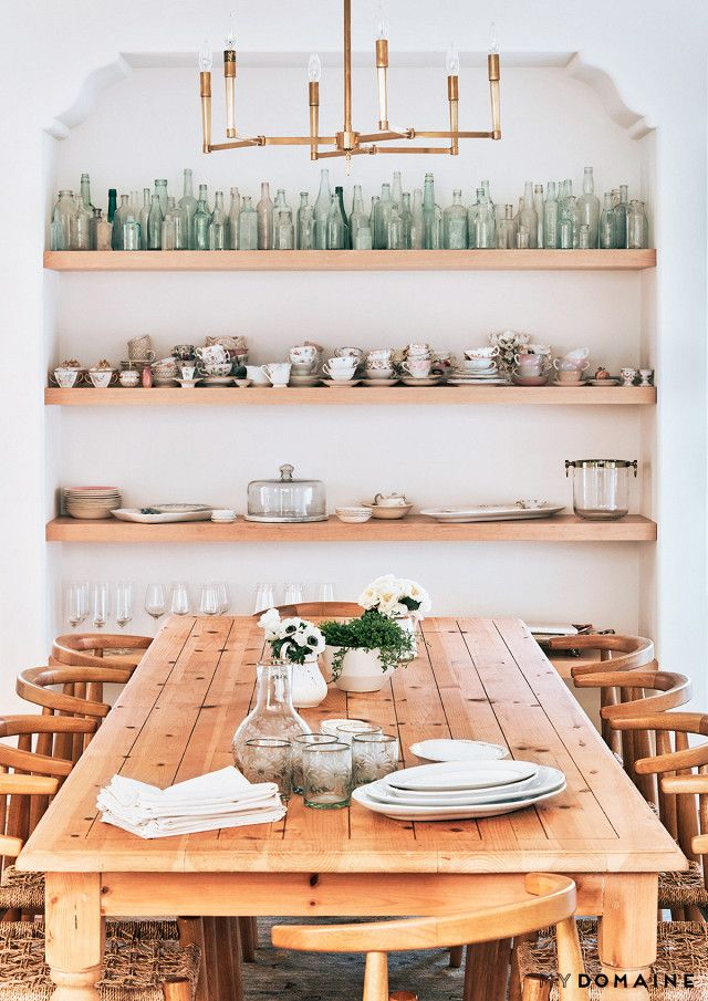 Lauren Conrad's dining room with a built-in  shelving with china and glasses, a bronze chandelier, a wooden table, and wishbone chairs