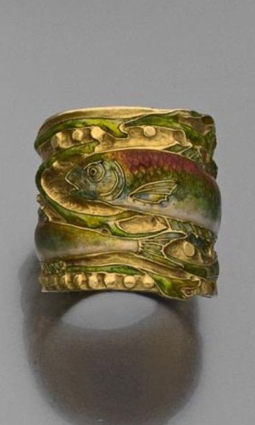 An Art Nouveau gold and enamel ring. The wide band decorated with fish amongst seaweeds. Monogrammed inside: A.LS.