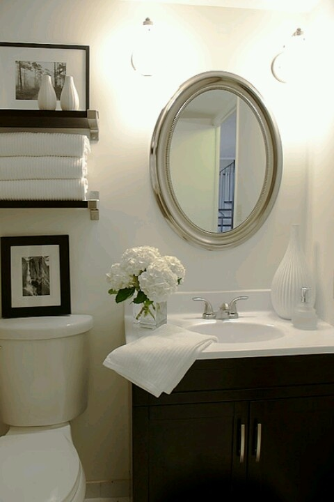 LOVE THE ENTIRE BATHROOM...ESP THE FLOWERS!! AND SIMPLE SHCES ABOVE TOILET. 20 BUCKS FROM TARGET W. SIMPLE WHITE TOWELS (RE BRAND cheap and fluffy after washed!) Use the frames I have already ...vases from TJ Maxx/homegoods...do it here and in new house! Masterbath too maybe/instead?