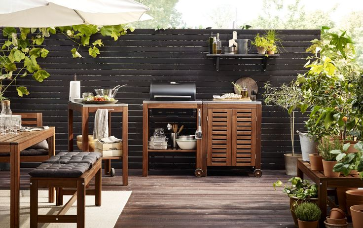 A patio with an outdoor kitchen consisting of a cart with an charcoal barbecue and a storage cabinet, all in brown stained solid acacia.