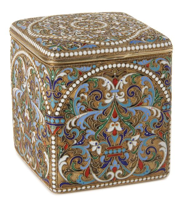 "A RUSSIAN SILVER-GILT AND CLOISONNE ENAMEL TEA CADDY, MOSCOW, 1899-1908. The side panels similarly enameled with scrolling foliage, strapwork and white beading on a stippled gilt ground. The hinged lid enameled with a quatrefoil medallion design of scrolling foliage and opening to reveal a brightly gilded interior hallmarked ""Moscow 1899-1908"", stamped in Cyrillic, LUBAVIN under the Imperial warrant, and 88 silver standard."