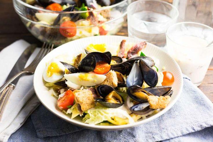 Recept voor caesarsalade voor 4 personen. Met witte wijn, ijsbergsla, kaas, brood, ei, ansjovis, mayonaise, knoflook, citroen, cherrytomaat, rode ui, komkommer en mossel