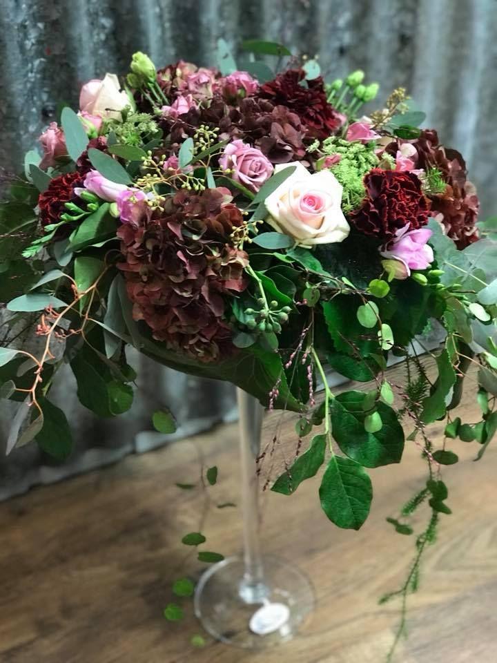 Muhkea syksyinen noutopöydän asetelma, jossa ruusua, hortensiaa, eucalyptusta, freesiaa, neilikkaa, krysantteemia, murattia, lankaköynnöstä ja liekoa.