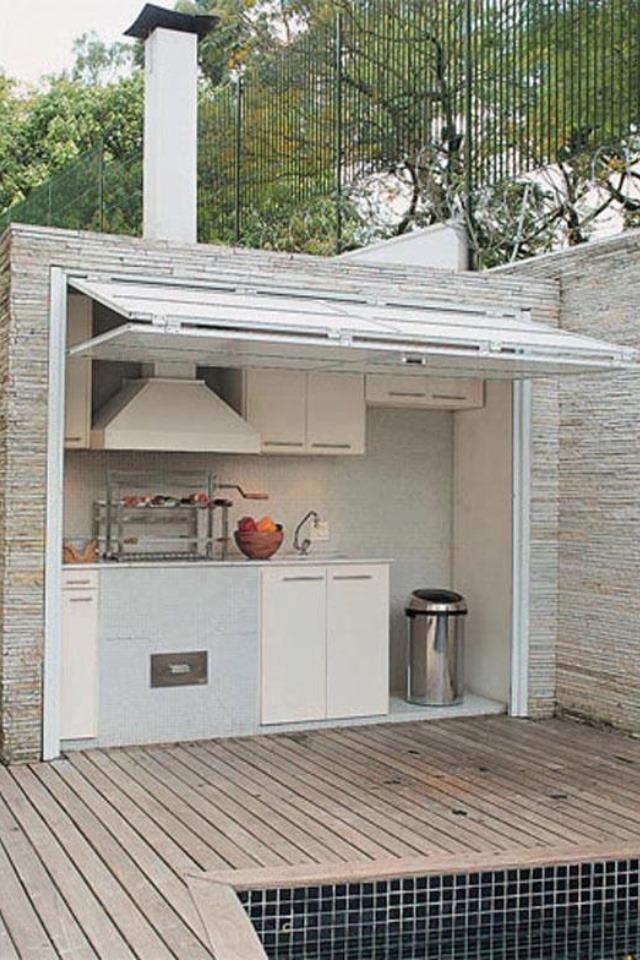 Outdoor kitchen BBQ area - love this idea with the garage door to shut everything away.