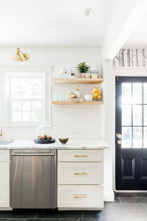White and gold kitchen features white shaker cabinets adorned with brass pulls paired with calcutta marble countertops and a white subway tile backsplash.