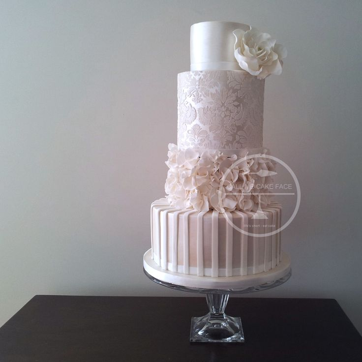 A Classic Cake Face Design of Pearl lustre and detailed in damask lace and white scrunch roses.