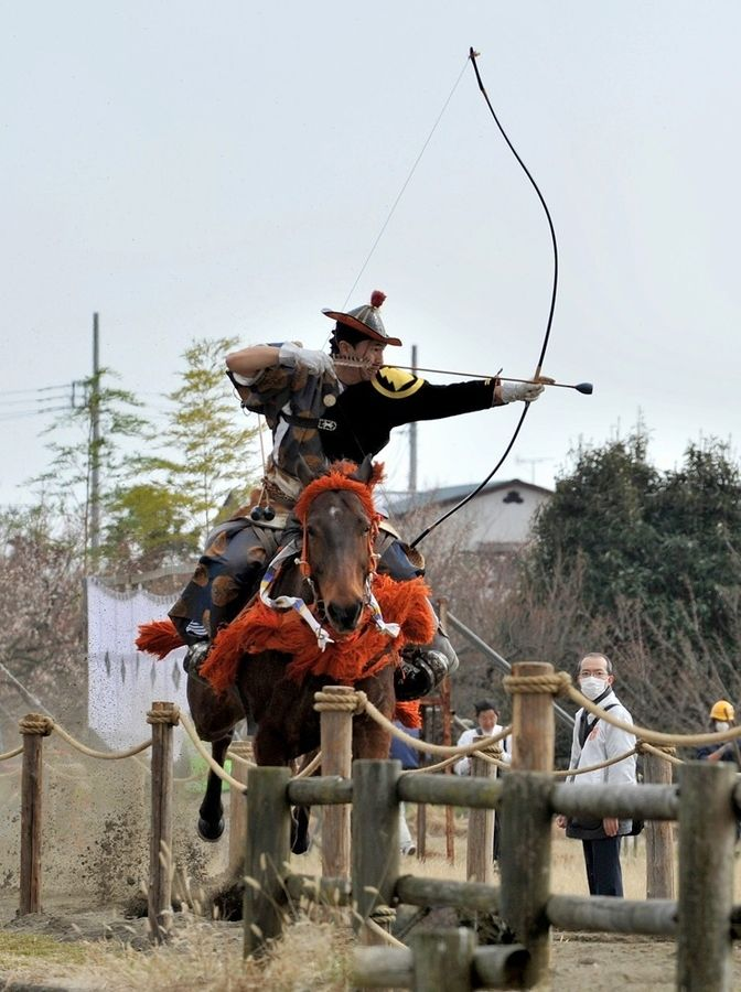 Yabusame archer taking aim at a target during a local festival in Kanagawa Prefecture, Japan.