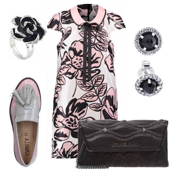 Vestito corto con fantasia floreale, manica corta e colletto rosa con profili neri. Mocassini in similpelle, con nappine, punta tonda, suola in gomma e tacco squadrato, il tutto in fantasia bicolore nei toni del vestito. Anello a forma di rosa nera con petali messi in risalto da brillanti. Orecchini a perno, neri con profili luminosi in brillanti. Clutch in finta pelle, monocromatica nera.