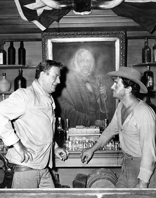 RIO BRAVO (1959) - John Wayne & Dean Martin discuss a scene in front of a painting of Texas hero Sam Houston - Directed by Howard Hawks - Warner Bros. - Publicity Still.