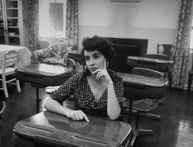 Peter Stackpole—Time & Life Pictures/Getty Images  Elizabeth Taylor sits at a desk in a classroom at Hollywood's University High School in 1950
