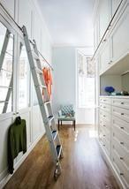 Inloopkast met gesloten kasten en ladder. Lichte inloopkast waarin bijna alles achter gesloten deuren zit. Erica George Dines