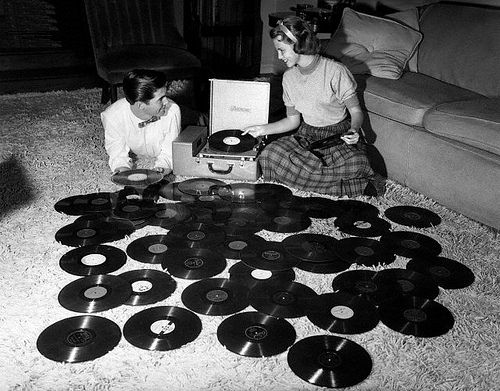 Young couple playing records spread out on living room floor. Ohio, 1955.