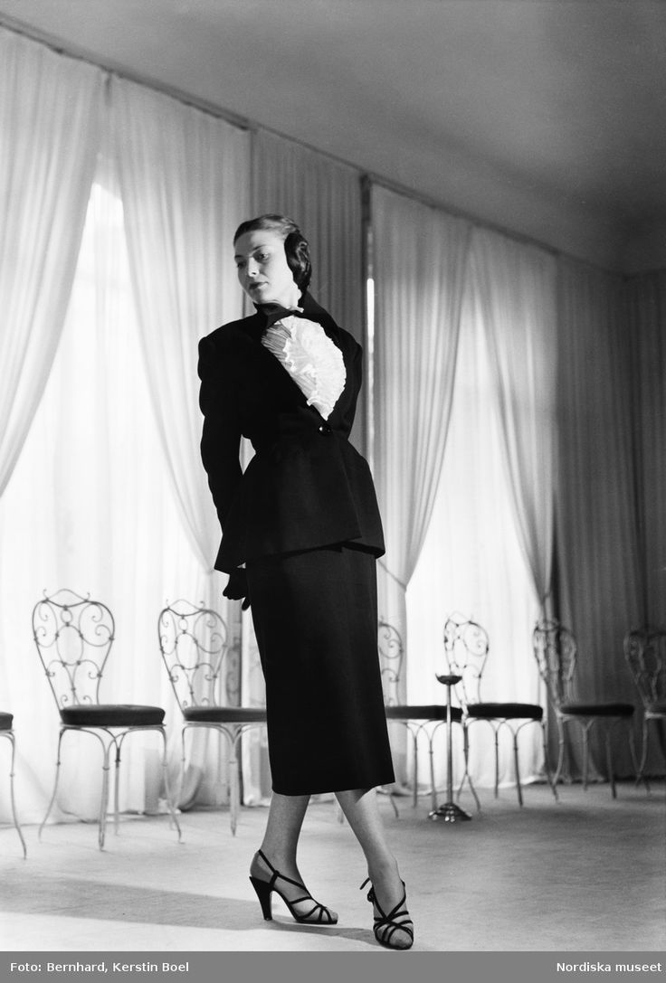 1947. Model klädd i mörk dräkt och vit blus med krås, mörka sandaletter. Stolar och ett askfat i bakgrunden. Fotograf: Kerstin Boel Bernhard