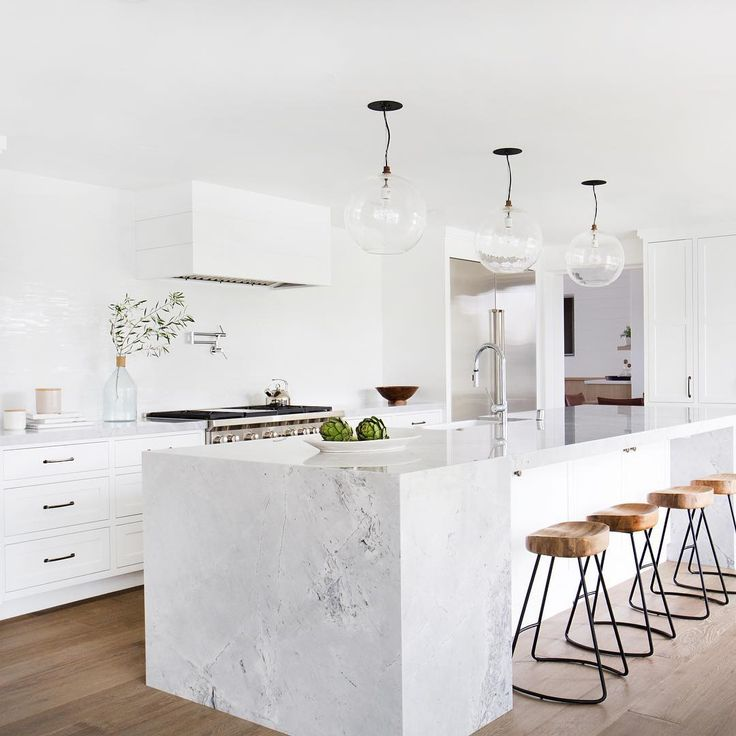 AFTER// all kids of perfect! Super white granite counters, glass pendants, wood bar stools from @wisteriahomedecor and customs gorgeous shaker style white cabinets. #aidbeforeandafter #clientsandycastles @tessaneustadt architecture @ericolsendesign construction @showalterconstruction