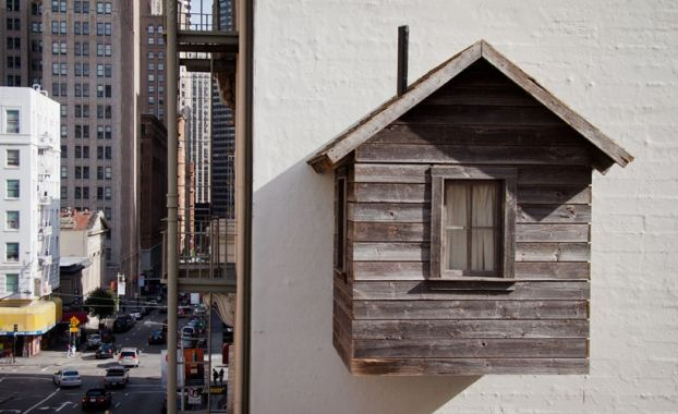 """Residential Architecture: Manifest Destiny! by Mark Reigelman: '""""..the project is a temporary rustic cabin which has been affixed to the hotel des arts, above and between other propertiesin the city's downtown core. floating approximately 40 feet in the air above the restaurant le central, the work stands as ananomalous-like outgrowth of the contemporary streetscape. the structure, which measures approximately W7 x D8 x H11 feet,  takes on a 19th-century architectural style. constructed…"""