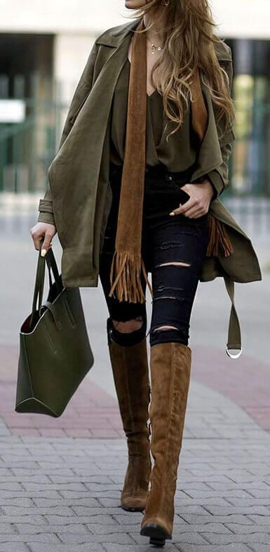 Woman wearing ripped black jeans, olive green top, olive green jacket, brown scarf, olive green handbag and brown boots