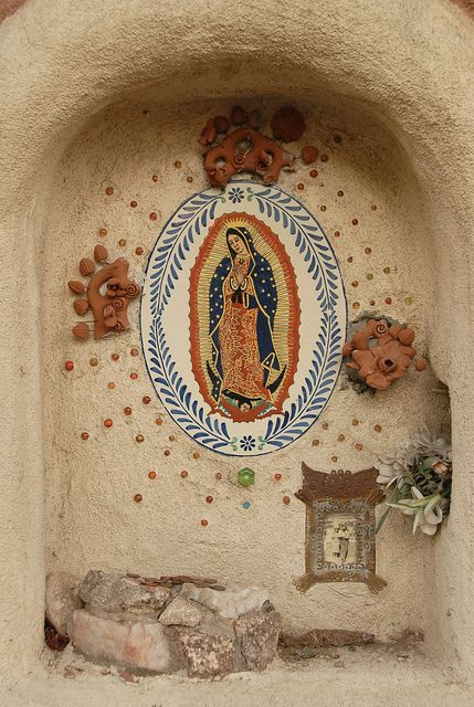 A niche in an adobe wall houses a shrine for the Virgin of Guadalupe in Santa Fe, New Mexico ~ Ilhuicamina via flickr
