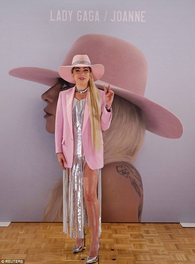 Pink lady: Lady Gaga posed in yet another pink hat on Wednesday at a photocall in Tokyo to promote her new album Joanne
