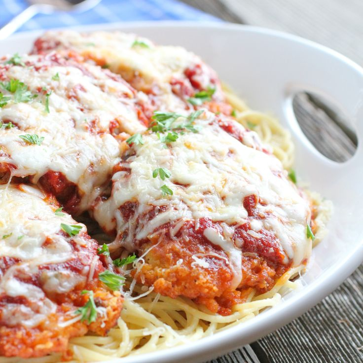 Oven-baked Chicken Parmesan with freshly-grated Parmesan cheese and Panko-breading on a bed of pasta. Easy, yummy dinner! Full recipe