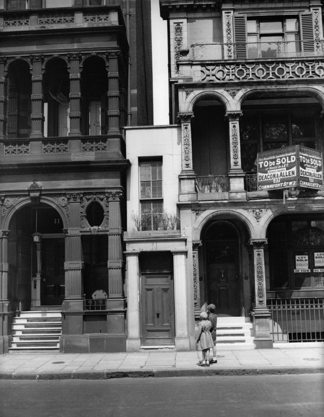 12 Jul 1933: Two girls come to view the smallest house in Knightsbridge, London - a tiny building nestled between two larger structures