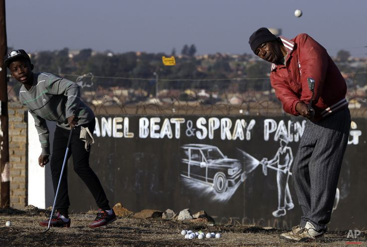 Atlehang Lebeloane, left, watches as his mentor Wynand Morudu, right, chips a shot during a game of golf at a park in Katlehong township, east of Johannesburg, South Africa, Thursday, July 16, 2015. (AP Photo/Themba Hadebe)