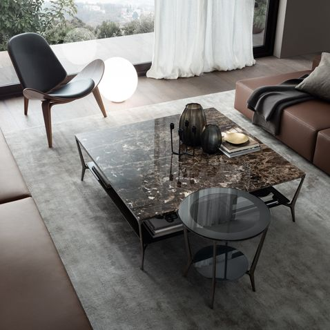 Planet round table with black nickel structure, grey transparent top, perimetral frame with silver finish. Squared coffee table with black nickel structure, emperador marble top