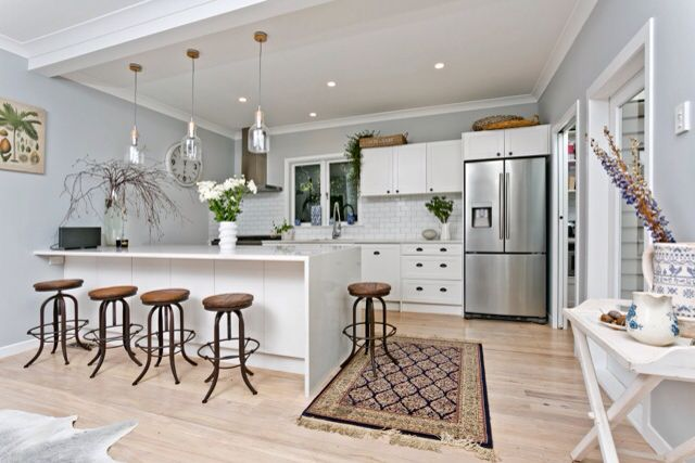 Open plan kitchen renovation in classic style. Central counter with marble finish serves as cabinetry and dining table. Glass hanging pendants for soft lighting, recessed spot LED spot lights for directional lighting.