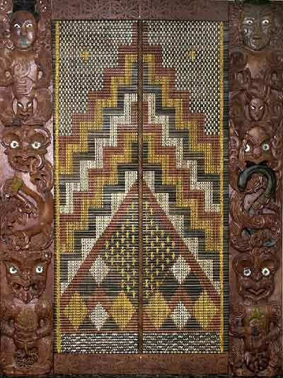 Image of Taonga Whakairo. This taonga is in three sections. These are a centre panel of tukutuku, flanked by two poupou. The work is rich in symbolism as it depicts the main gods of the Māori pantheon that are associated with our work. The work is also a symbol of LINZ's historic past and of its core business today, of being the kaitiaki (guardian) and interpreter of land information, for New Zealand.