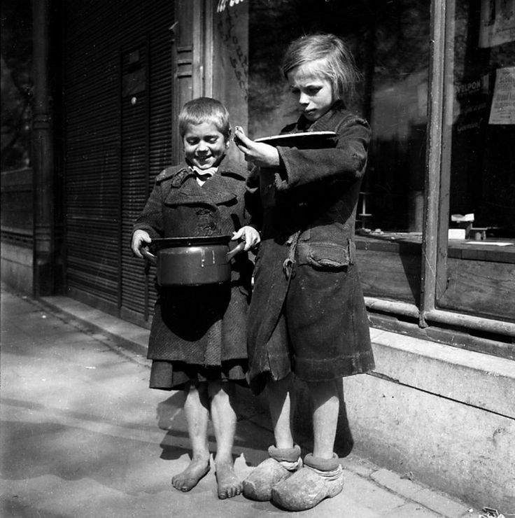 """Dutch children are provided with bread and soup during the Hongerwinter (""""Hunger Winter"""") famine of 1944-1945. Towards the end of the war, food supplies became increasingly scarce in the Netherlands. Some 4.5 million Dutch citizens were affected by the famine; about 22,000 died as a result. Amsterdam, North Holland, Netherlands. November 1944. Image taken by Cas Oorthuy"""
