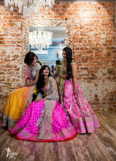 bridesmaids , elegant sister of the bride outfits , pink floral lehengas, girly pastel lehengas, engagement lehenga , sangeet lehenga , excited bridesmaids , brick wall , mirror chandelier , giggling brides , bridesmaid photos